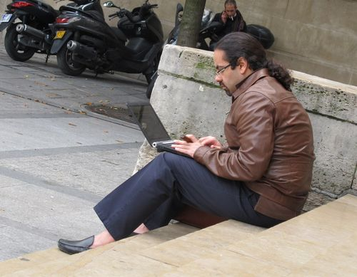Man Smoking Cigar and Typing on Laptop Rue St. Honore