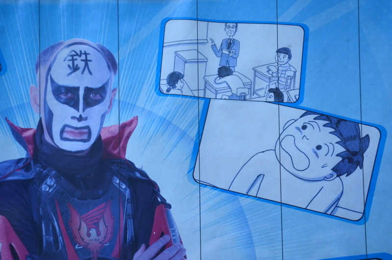 Yanaka poster with odd supervillian outside school detail